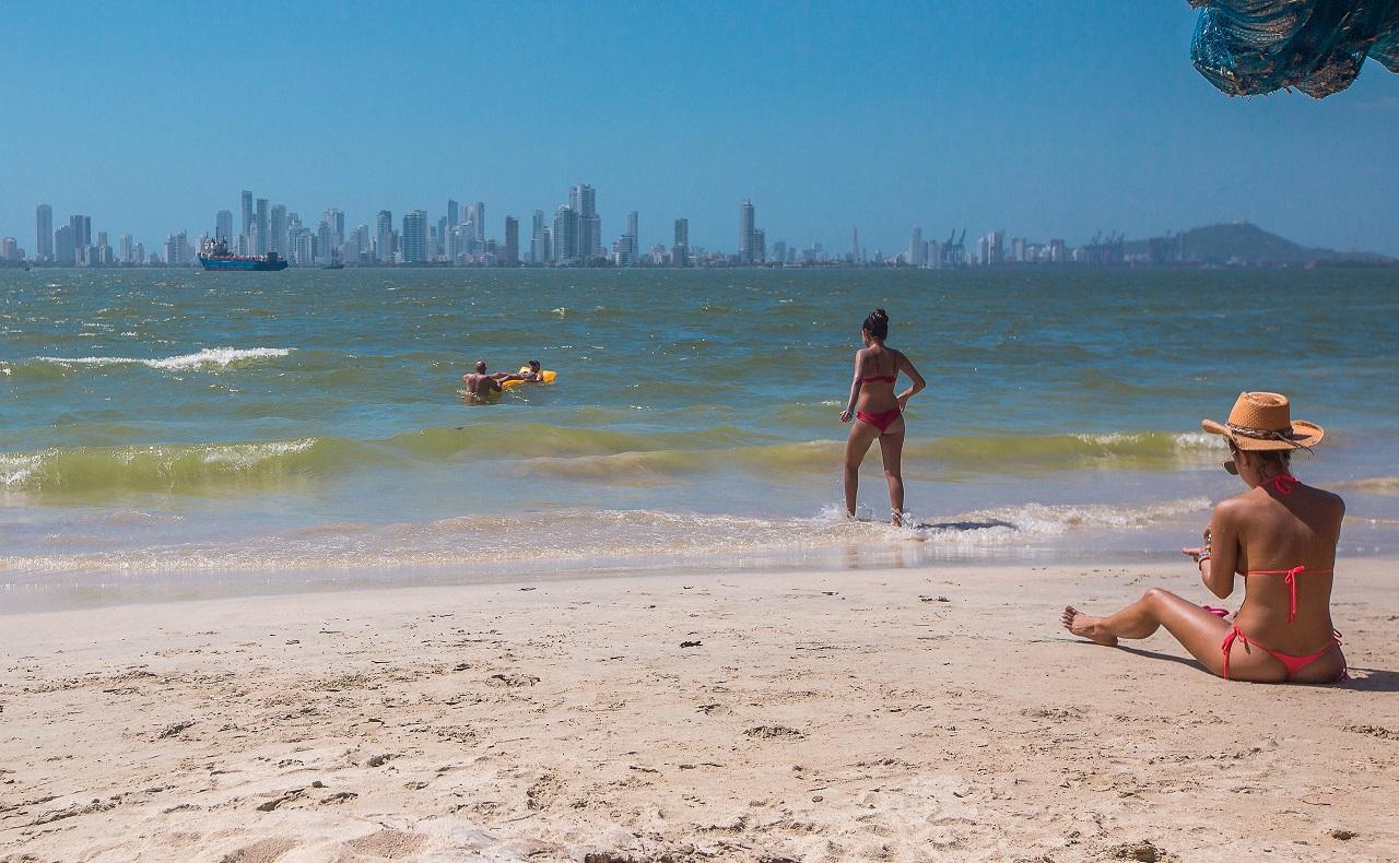 Turista bronceándose en playa de Tierrabomba con la vista de Cartagena