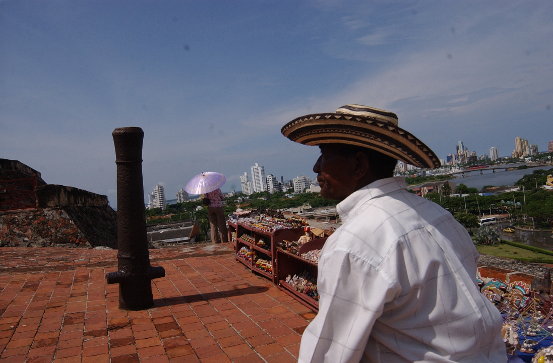 Cañón en posición vertical en el Castillo de San Felipe con vendedor a su lado