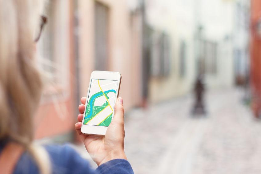 Turista usando una aplicación de geolocalización mientras camina por la calle