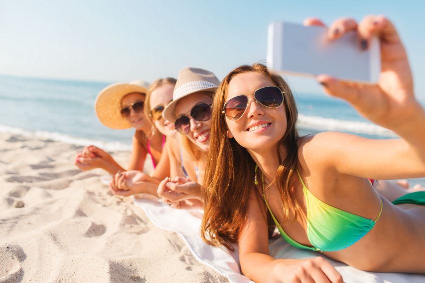 Grupo de jóvenes mujeres se hacen una selfie mientras toman el sol en una playa de arena blanca