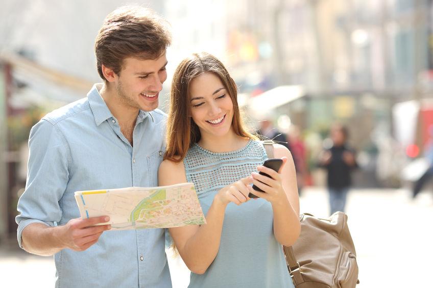 Pareja de turistas consultando un mapa de papel y mirando en un smart phone
