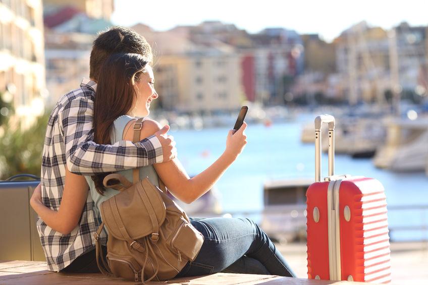 Pareja de turistas sentados con su equipaje mientras consultan su teléfono móvil en busca de hoteles y pasajes