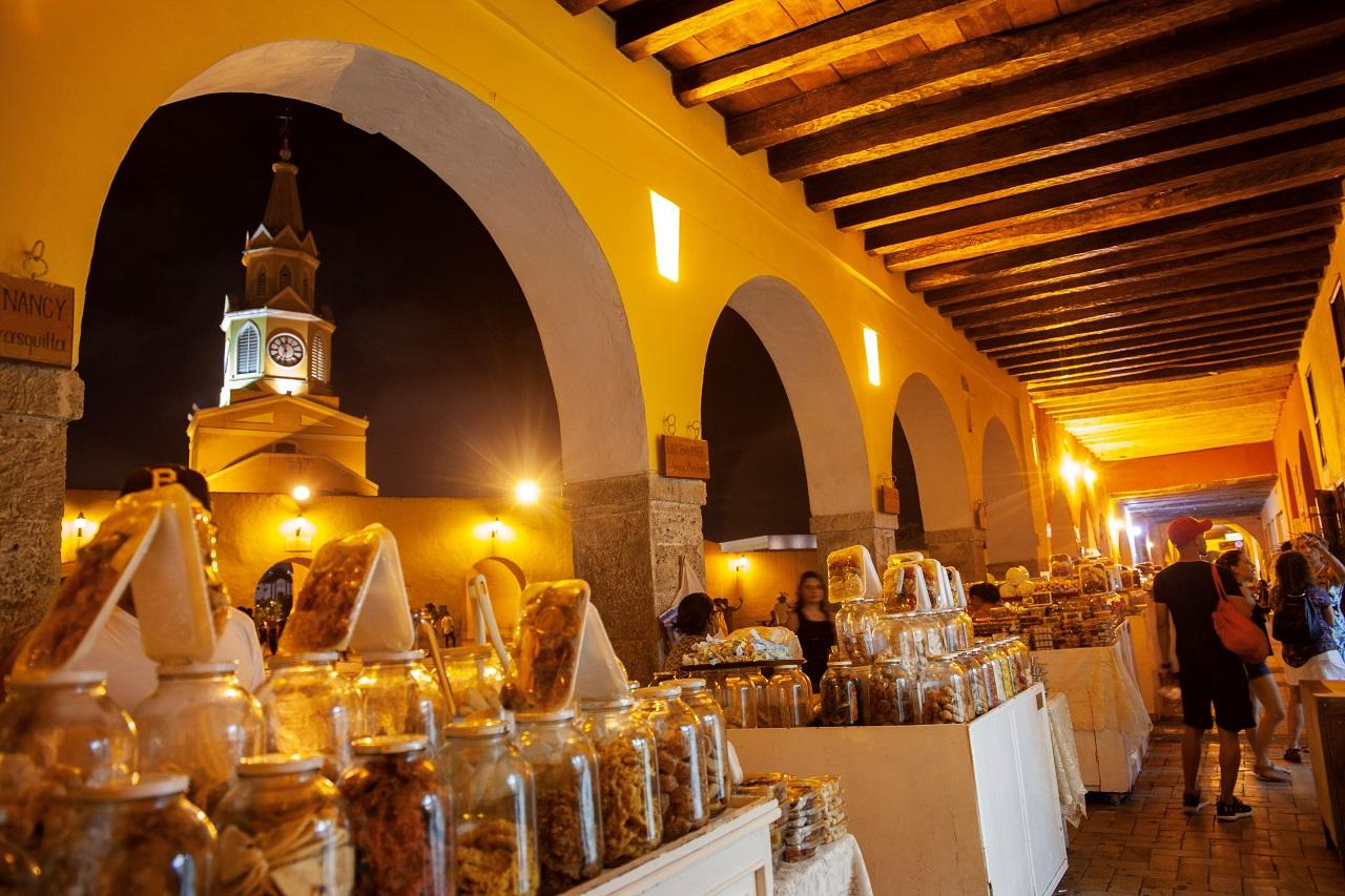 Imagen nocturna de El Portal de los Dulces con la Torre del Reloj de fondo