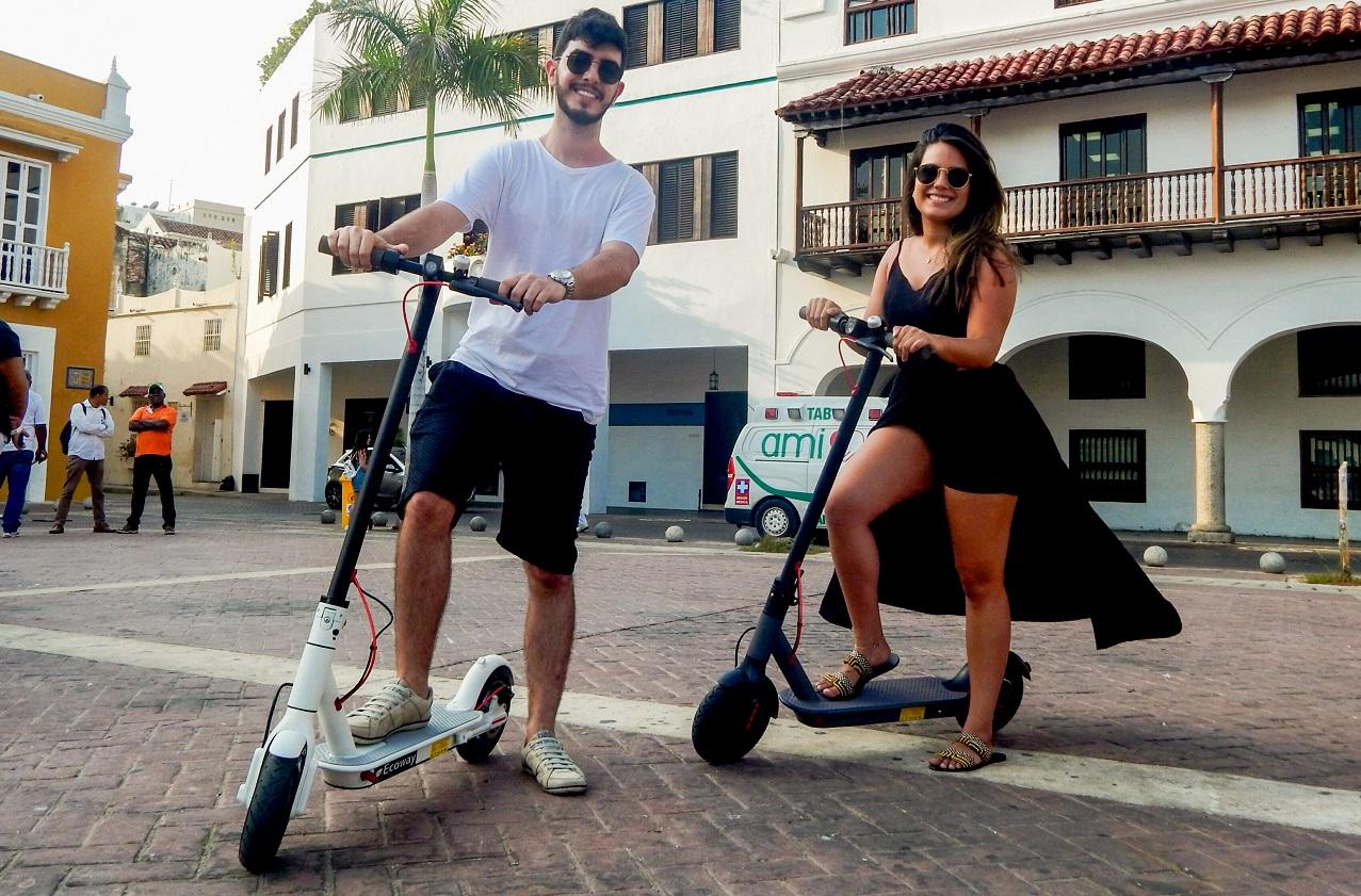 Pareja posando con scooters de Ecoway Tours en el centro de Cartagena