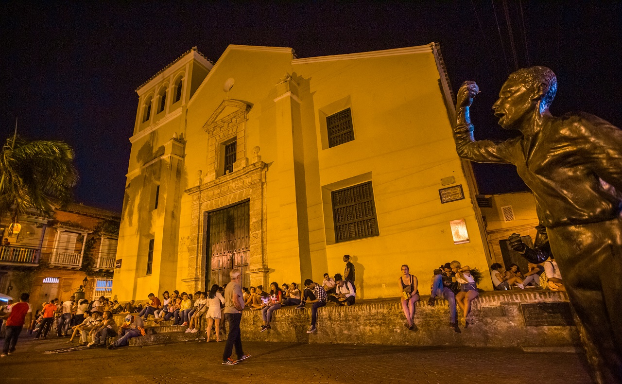 Gente departiendo en la Plaza de la Trinidad en Getsemaní con la Iglesia de la Santísima Trinidad de fondo imagen nocturna