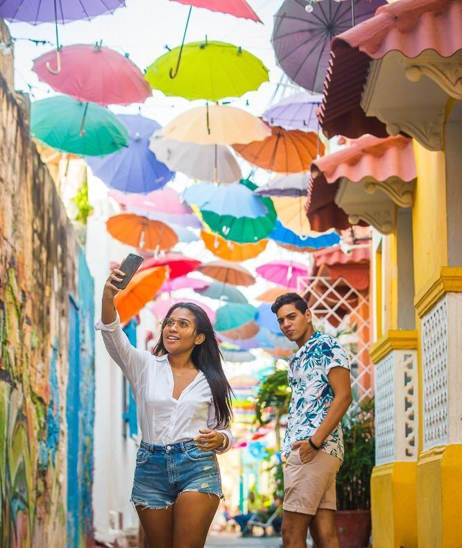 Pareja haciendose selfie en el callejón angosto o calle de las sombrillas en el barrio Getsemaní de Cartagena