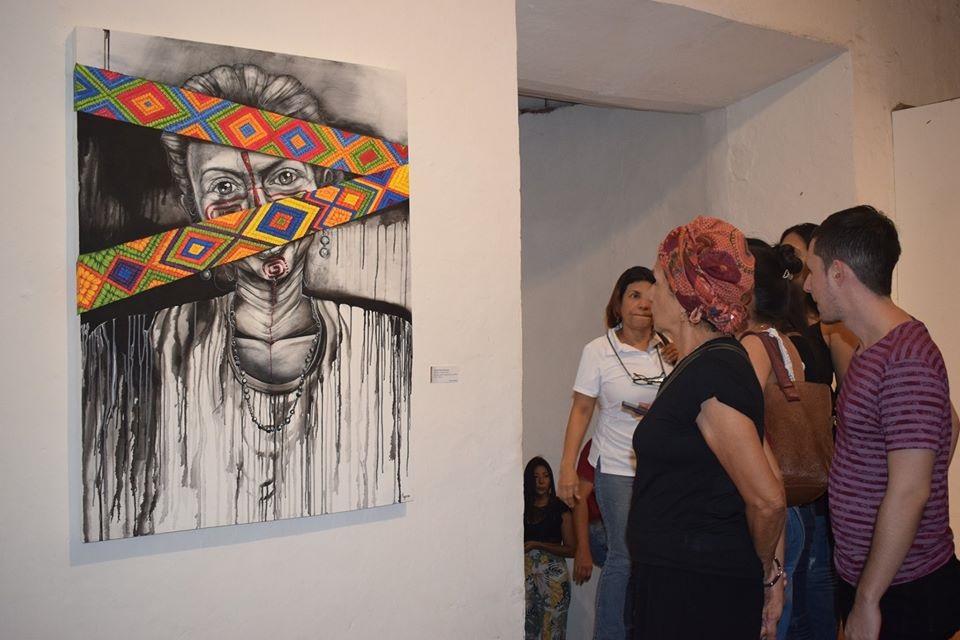 Personas admirando exposición de pintura en el Santuario de San Pedro Claver en Cartagena
