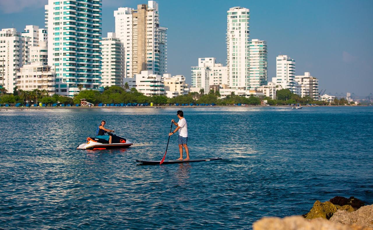 Hombres en moto acuática y paddle board en las playas de Cartagena, imagen para ilustrar nota sobre deportes acuáticos