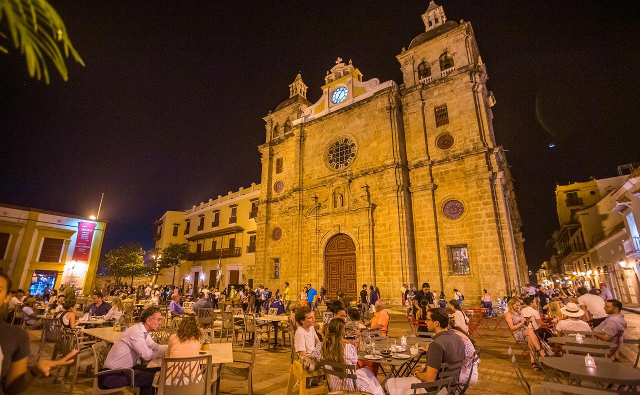 Turistas departiendo durante la noche en la Plaza de San Pedro Claver en Cartagena, imagen para ilustrar nota sobre destinos turísticos