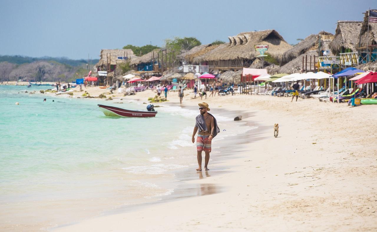 Hombre caminando por la playa con sombrero y lentes de sol, imagen para ilustrar nota sobre protección de la piel