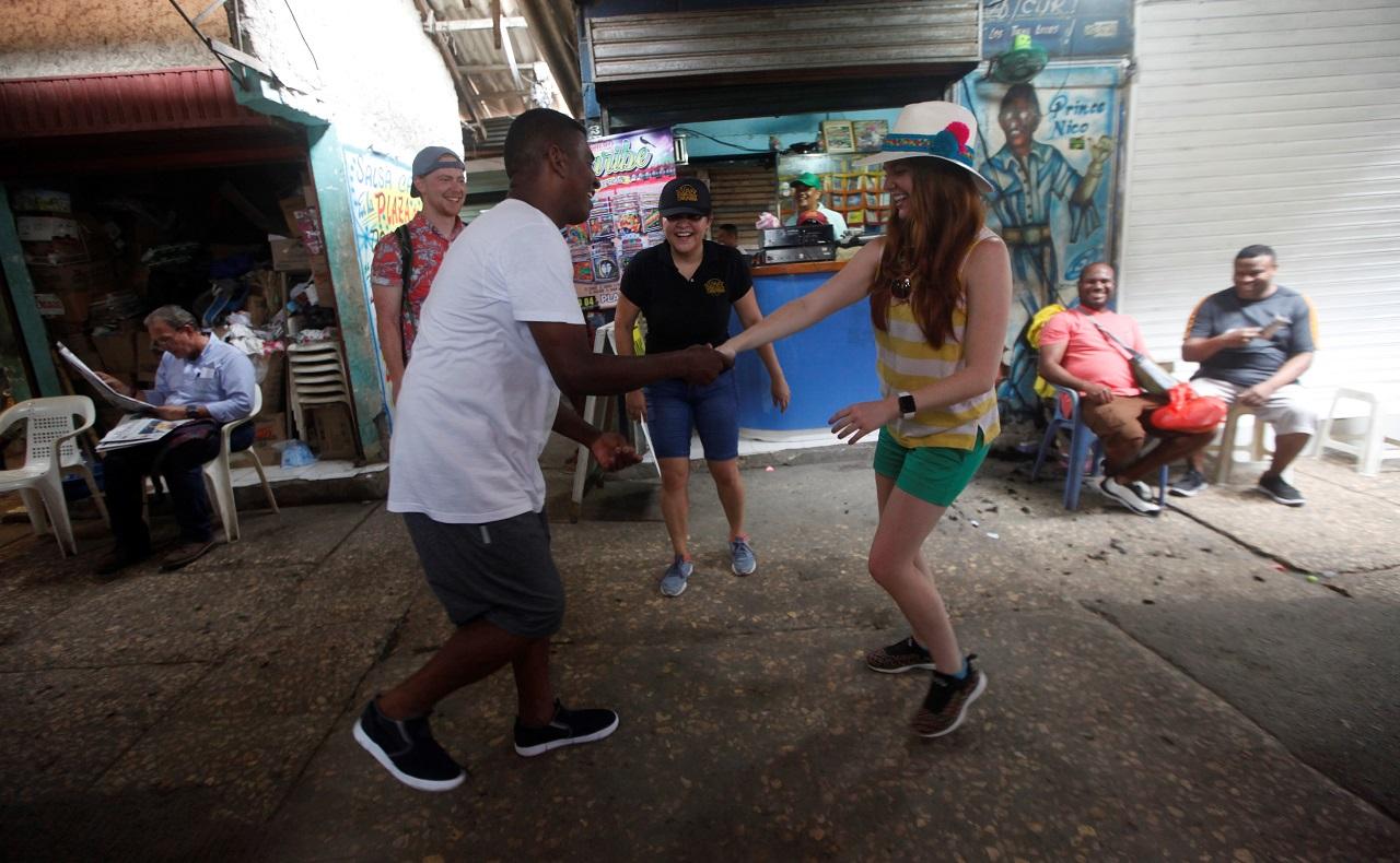 Pareja de turistas norteamericanos recorriendo el Mercado de Bazurto en Cartagena, bailando champeta