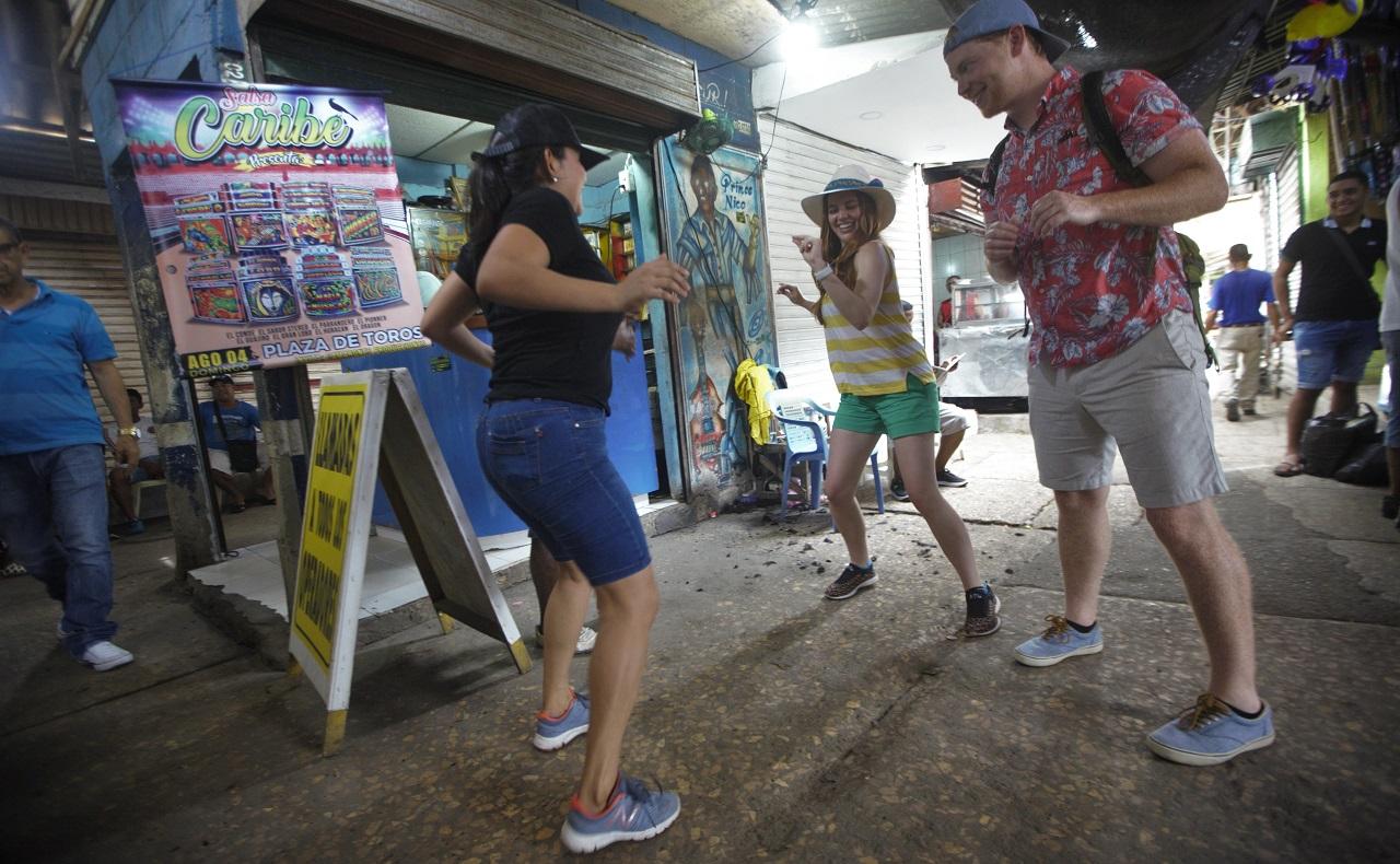 Pareja de turistas norteamericanos recorriendo el Mercado de Bazurto en Cartagena, baile de champeta