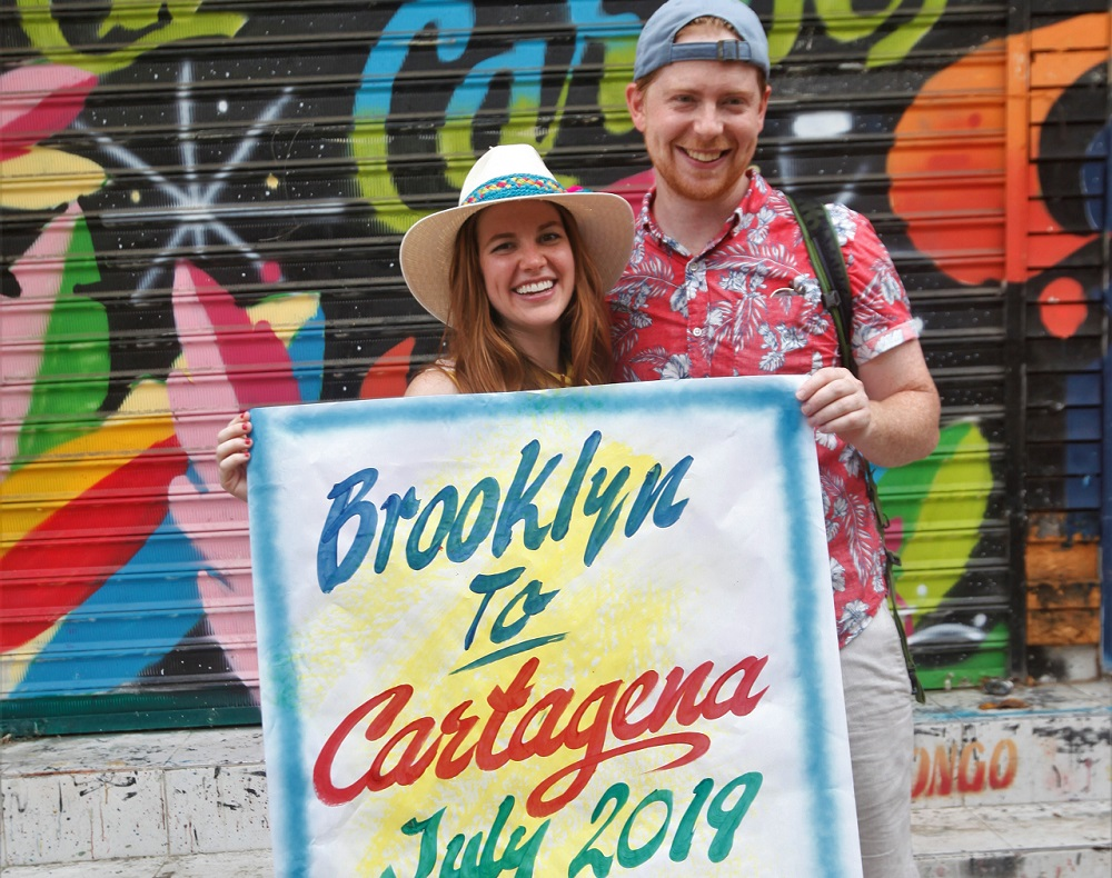 Pareja de turistas norteamericanos recorriendo el Mercado de Bazurto en Cartagena, posando con cartel tradicional personalizado