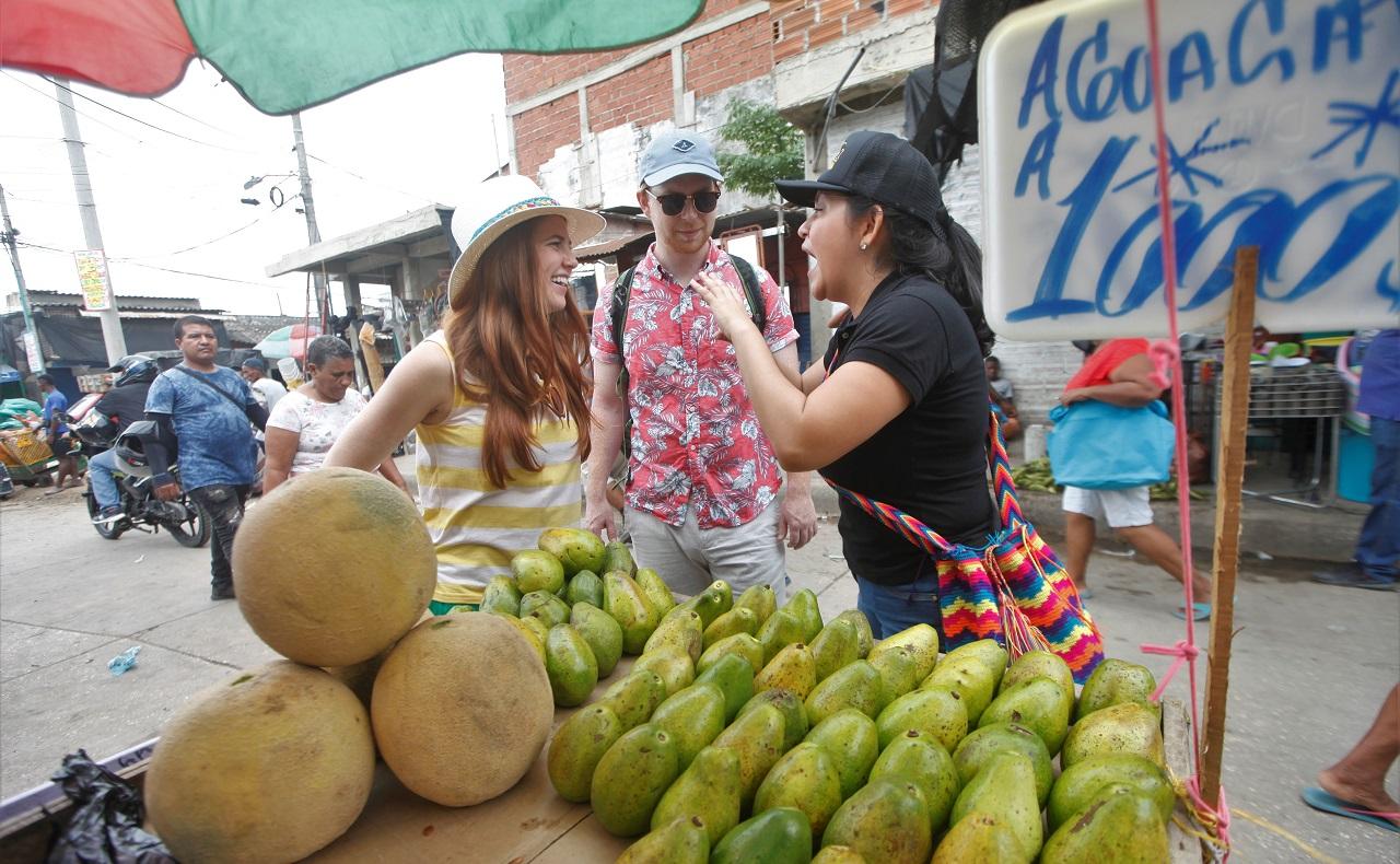 Pareja de turistas norteamericanos recorriendo el Mercado de Bazurto en Cartagena, puesto de aguacates