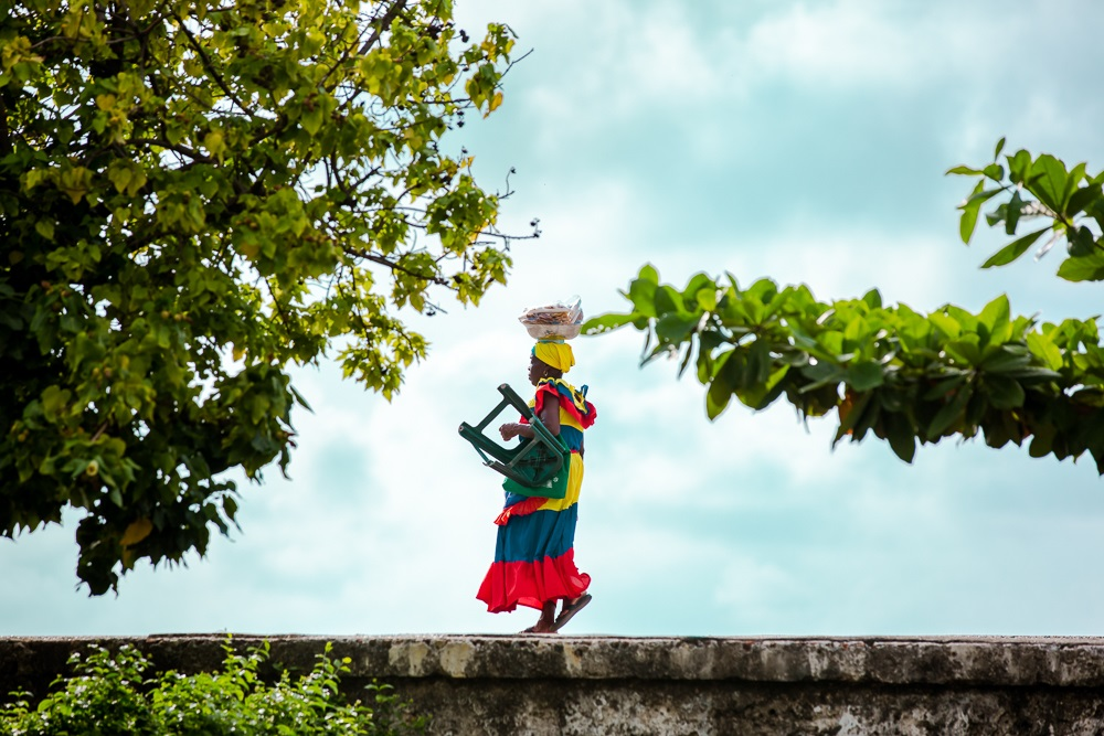 Palenquera caminando sobre muralla del Centro Histórico de Cartagena