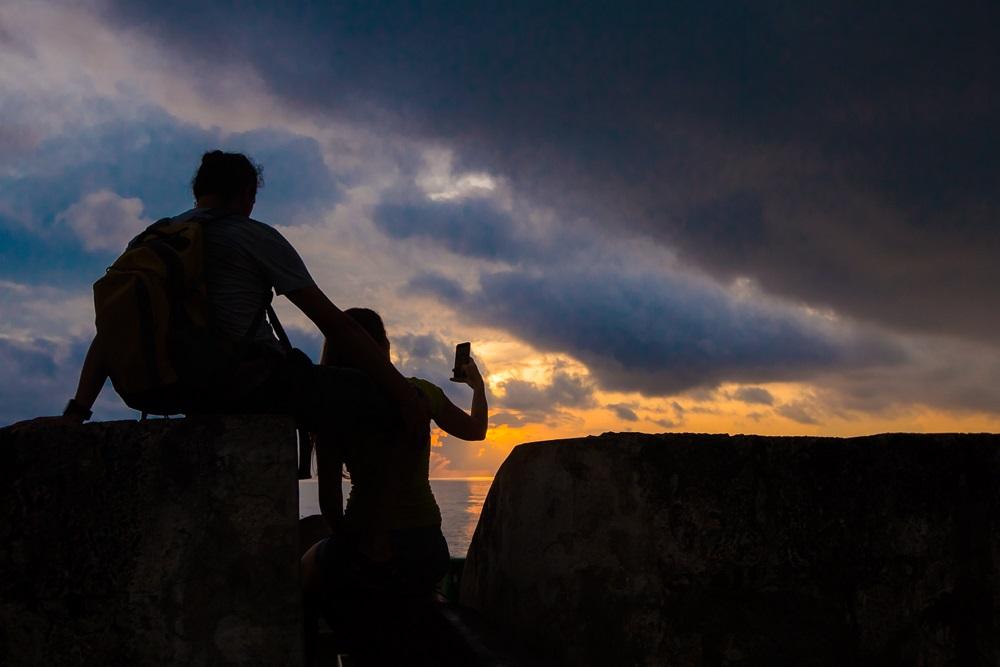 Pareja fotografiando el atardecer en sector de las murallas, imagen para ilustrar nota del día del amor y la amistad en Cartagena
