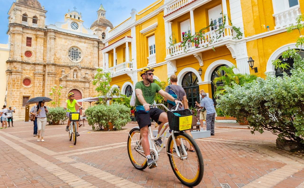 Turistas en bicicleta por la Plaza de San Pedro Claver, imagen para ilustrar nota sobre plazas de Cartagena