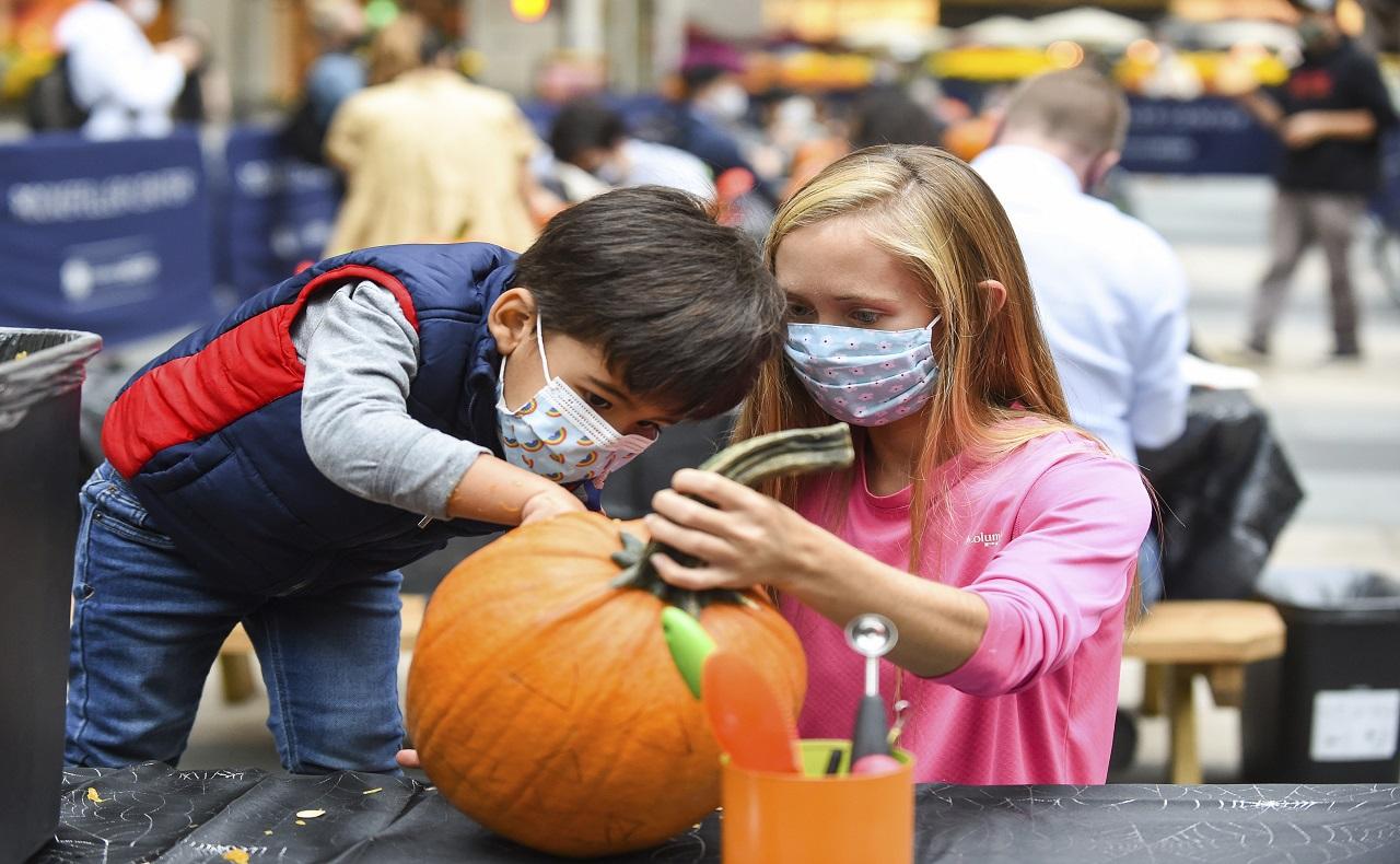 niños decorando una calabaza para la noche de halloween